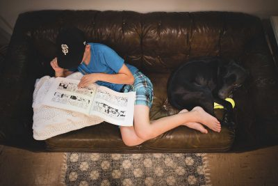 little boy reading comic book with black lab dog