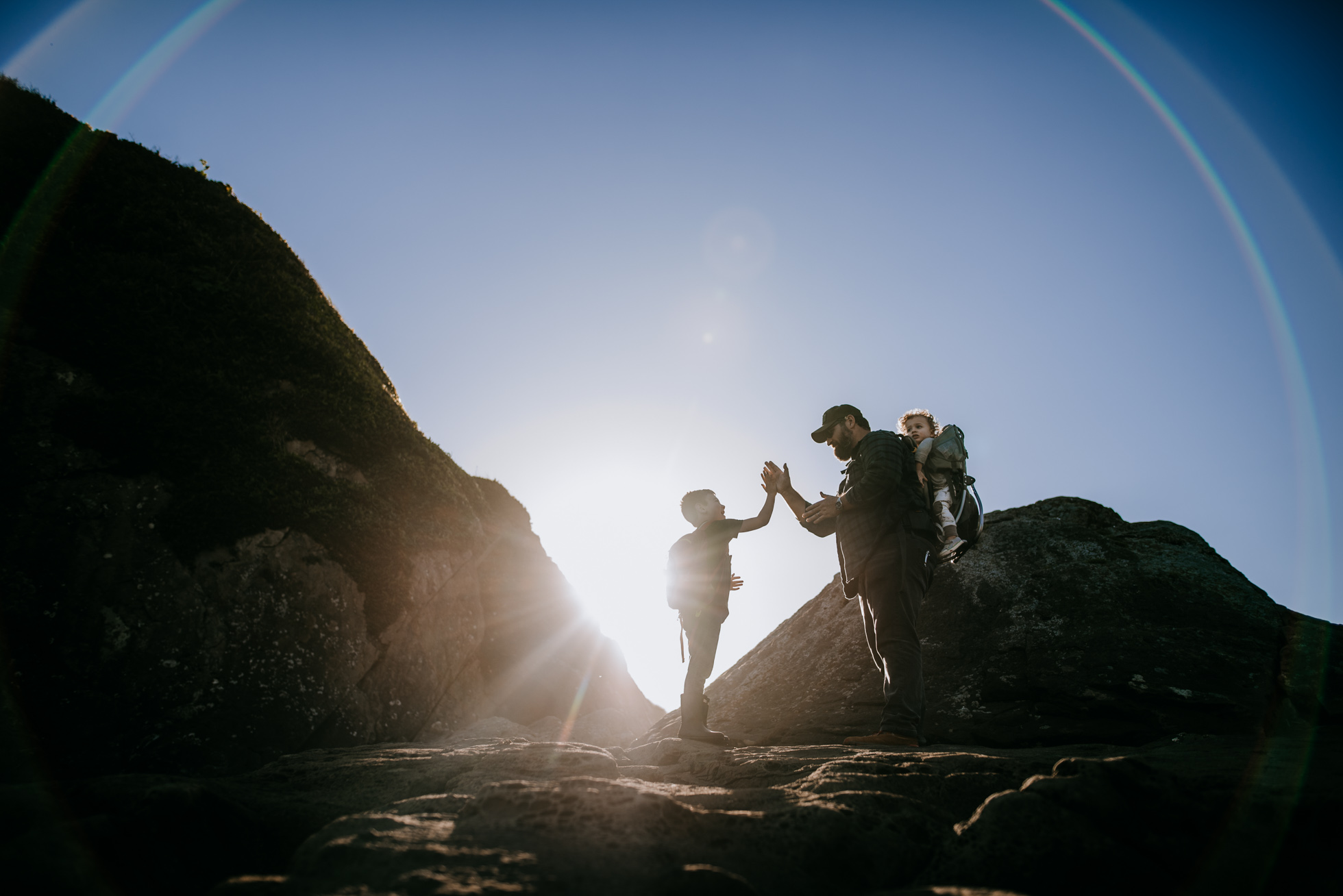 Boys and their father playing at the top of a rock on the Washington coast at sunset.