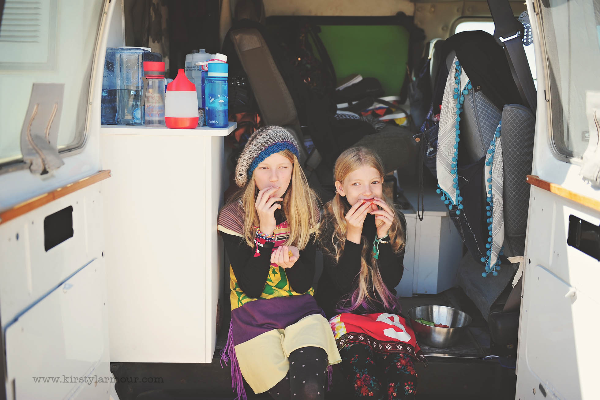 2 girls eat lunch perched inside the doors of the van they live and travel in