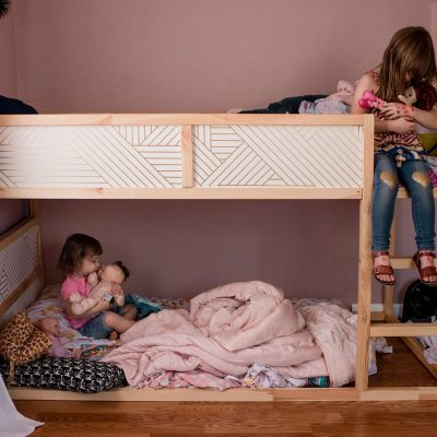 Documentary photography of two sisters playing with dolls