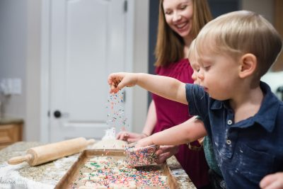 twin boys using sprinkles while baking cookies
