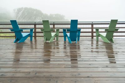 blue and green chairs on deck in fog