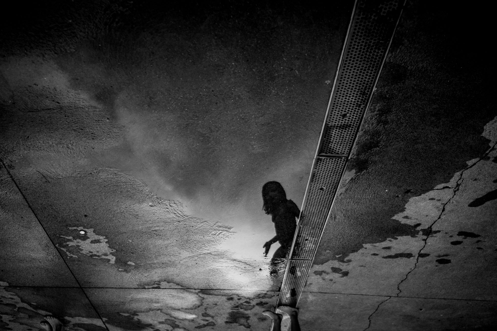 Girl Reflection Flipped In Black And White Puddle