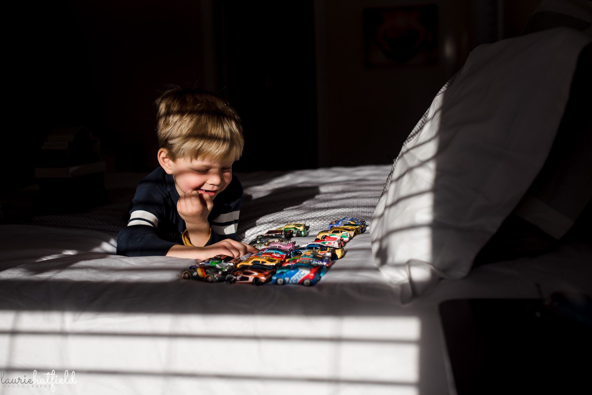 4-year-old playing with race cars on bed