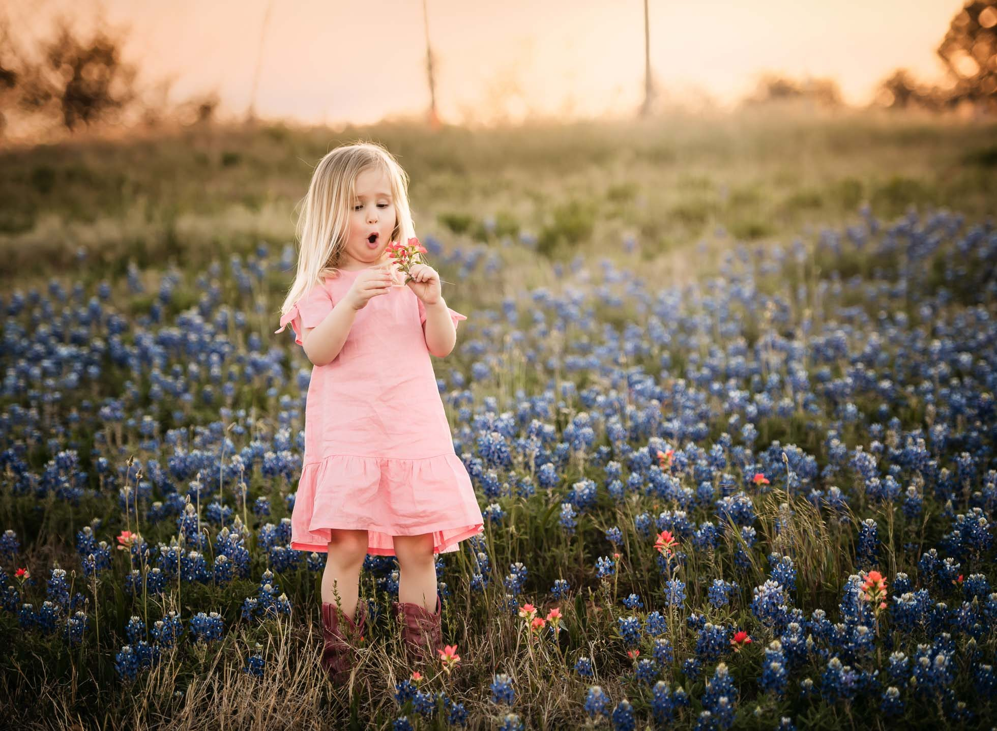 she has the best expressions blonde girl toddler in field of bluebonnets edmond ok photographer oklahoma city natural light photographer kate luber photography