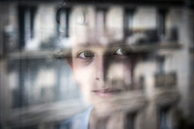 Portrait of a young boy looking through a window in Paris