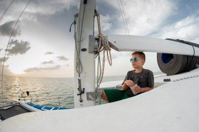 Boy on catamaran at sunset in the Caribbean islands.