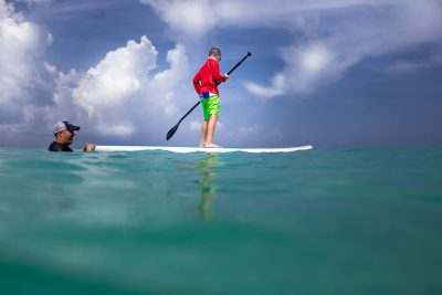 Boy in red shirt paddling on SUP in the Caribbean Sea.
