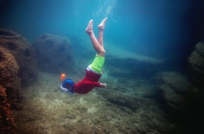 Boy in red swim suit with full faced snorkel diving in the ocean in Grand Cayman.