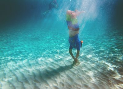 Boy snorkeling in the ocean with sandy shore and light rays.
