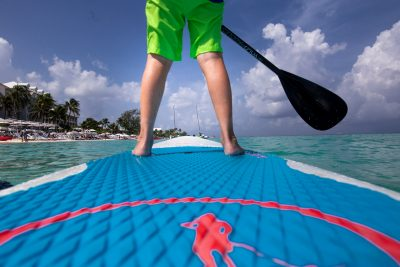 Boy standing on YOLO paddle board with red, blue and green in the Caribbean Sea.