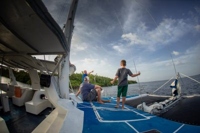 Father and son on the font of a sailing catamaran in the ocean.