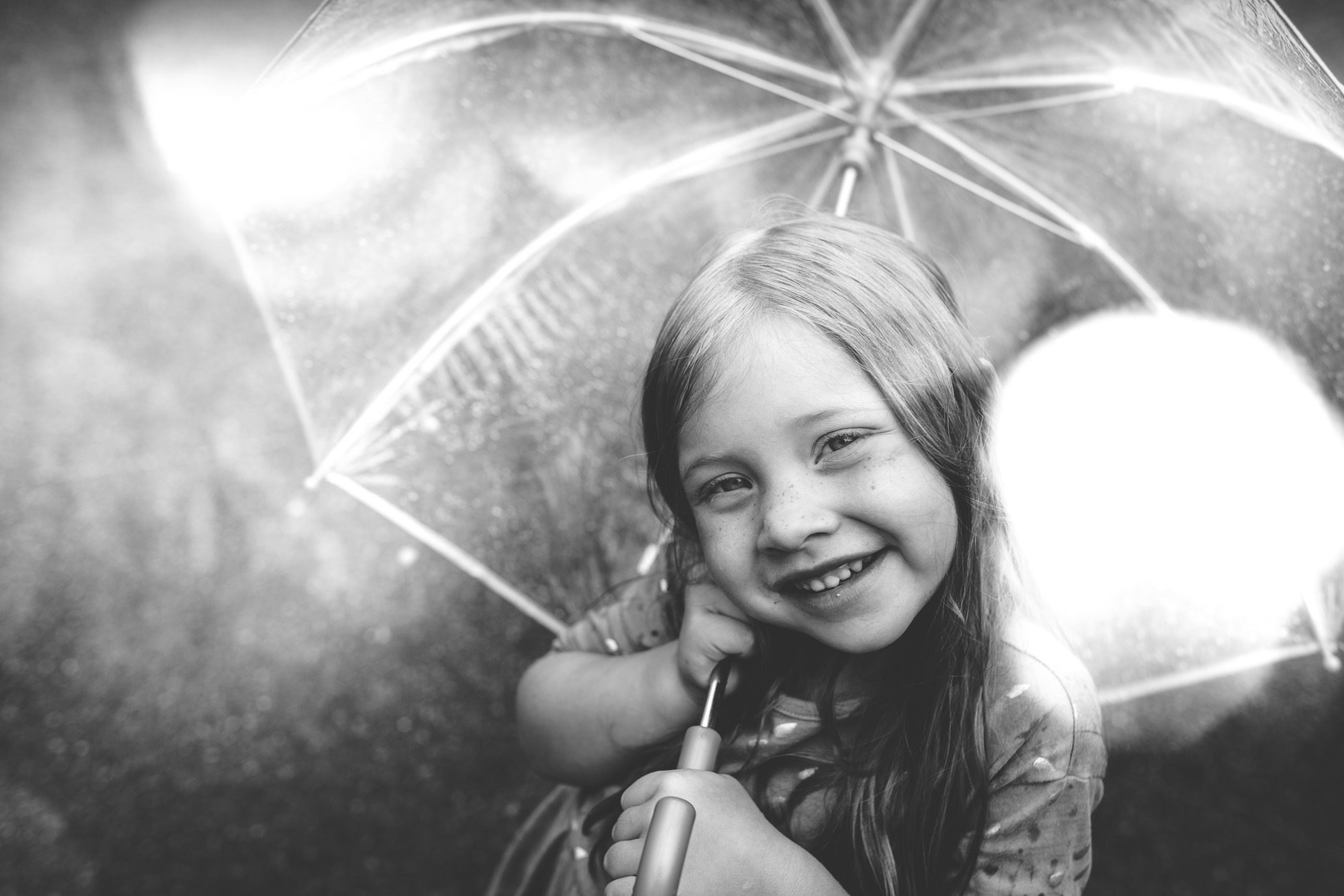 girl with umbrella in rain black and white by tiffany kelly