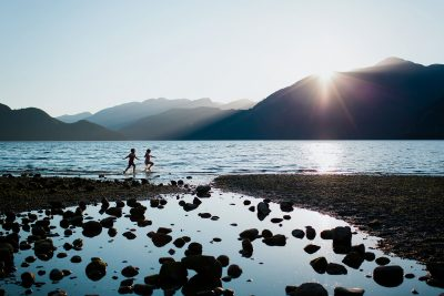 Two kids run along the coastline in a beautiful landscape of ocean, mountains, and a setting sun.