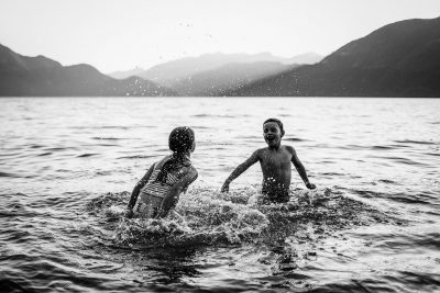 Black and white image of children splashing int eh ocean with a stunning mountain backdrop.