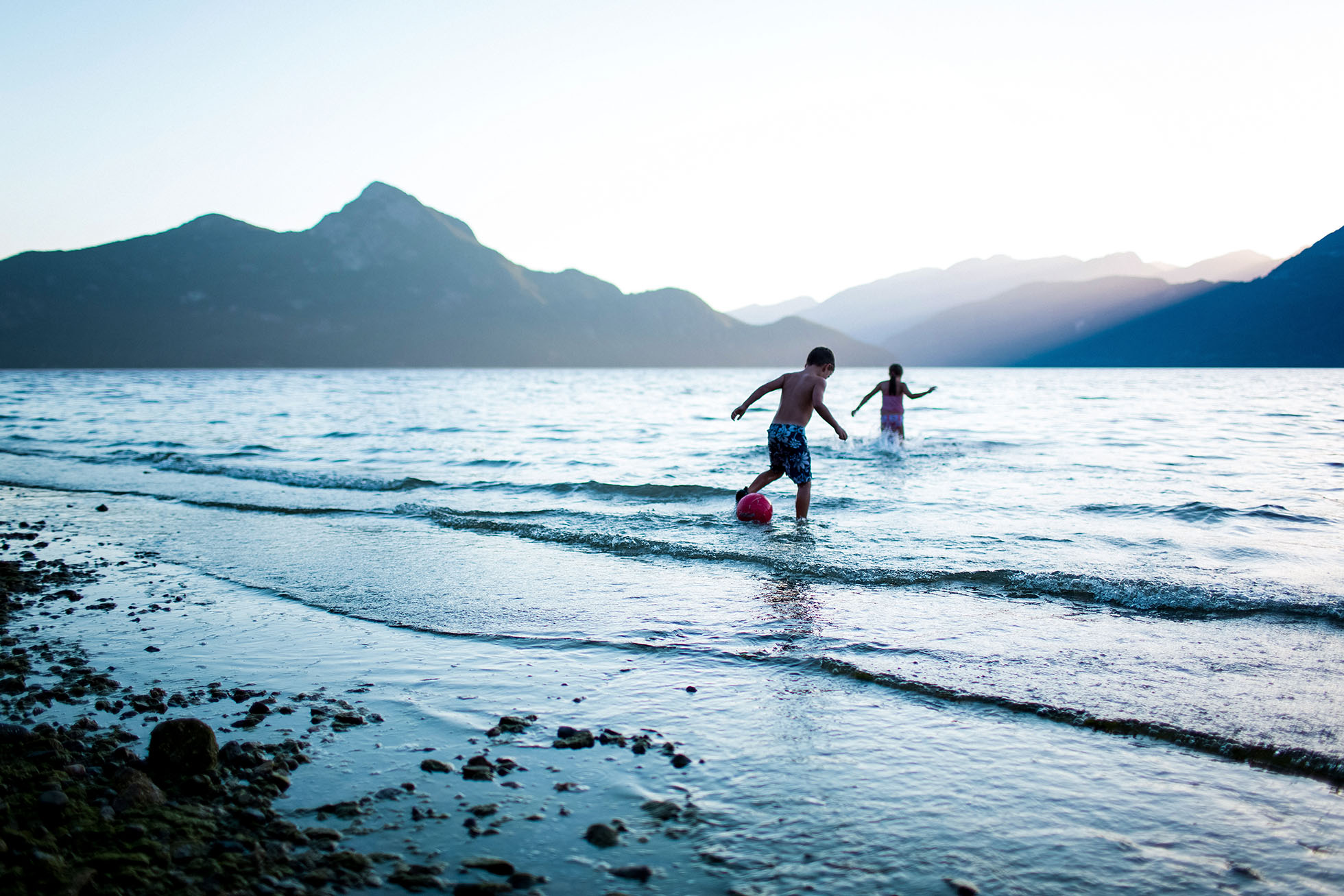 Two children playing in the ocean with a mountain backdrop.