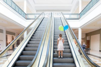 Little girl holding balloons riding up escalator to Nordstrom at mall