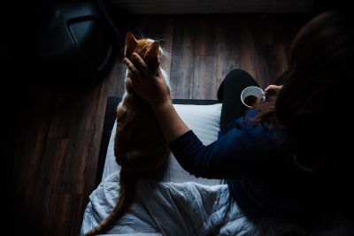 A woman pets her cat while holding a cup of coffee in her Edmonton apartment