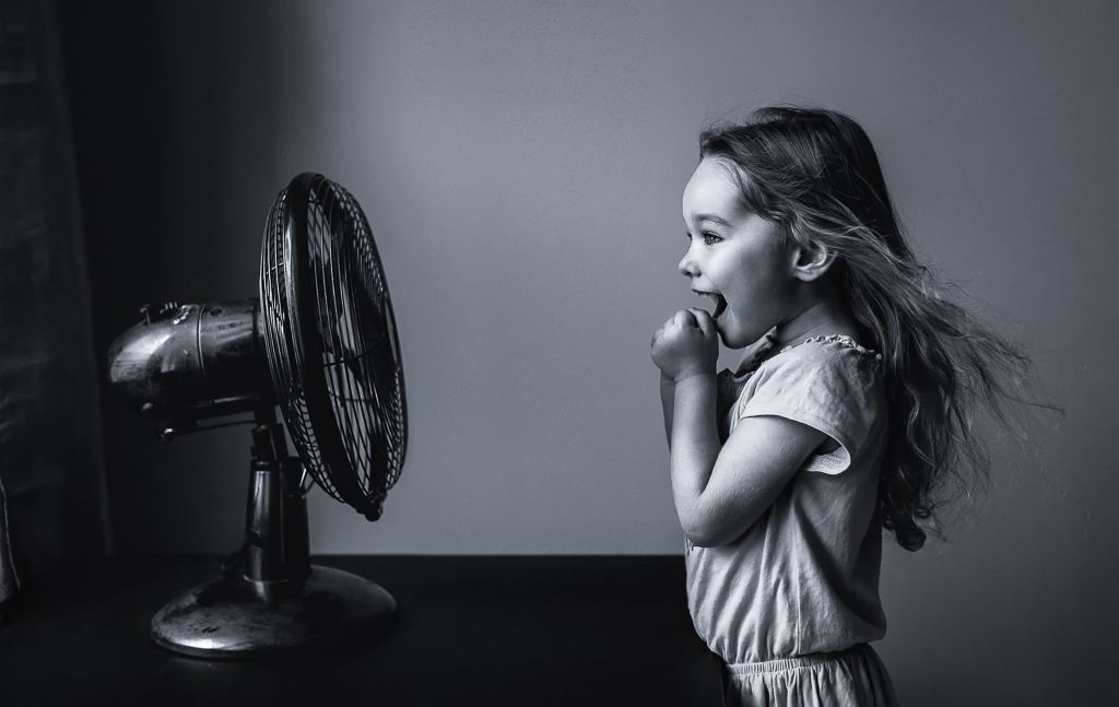Girl is standing in front of a retro style fan while it blows her hair in black and white