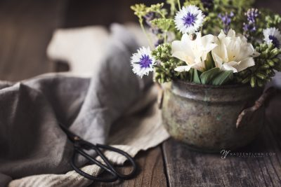 flowers in a green pot with linen and shears