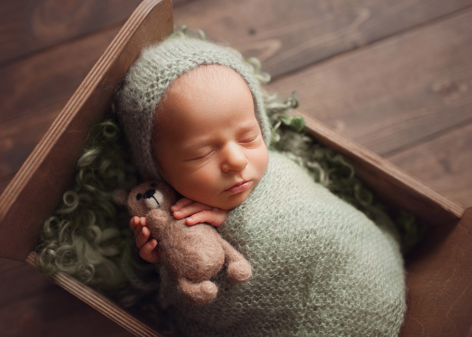 Cleveland Ohio Newborn photographer poses newborn in prop using sage green wrap and bear lovey