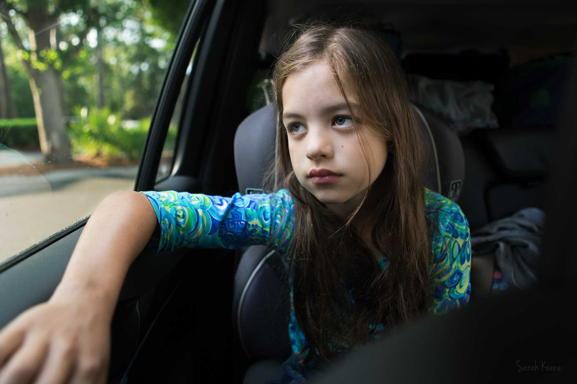 Documentary photojournalistic photograph of a child in the family SUV