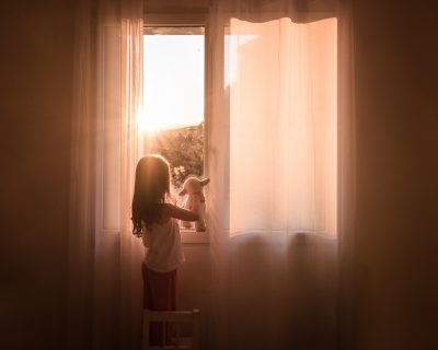 Girl looks out of bedroom window in evening time with her cuddly toy