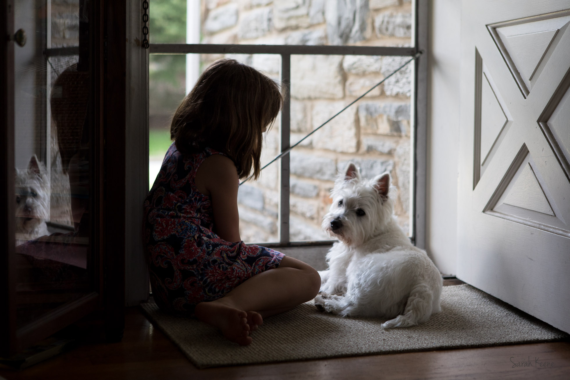 Child with West Highland Terrier by open door