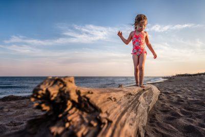 Girl balancing on a drift wood log at the beach at sunset