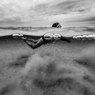 blackandwhite-girl-swimming-gopro-split-underwater-shot-lindsayberos