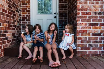 Children eat ice-cream on front porch.