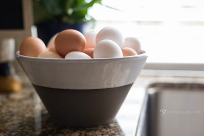 brown and white eggs in a brown and white bowl on the sink drain