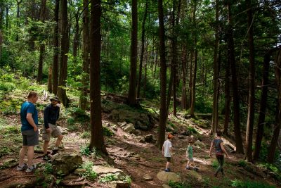kids and adults hiking through the woods