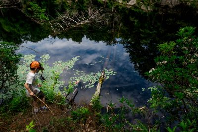 boy with hiking stick standing by a reflective pond with lily pads