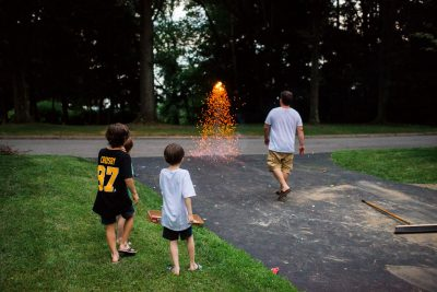 man setting off fireworks in the street for the neighborhood kids