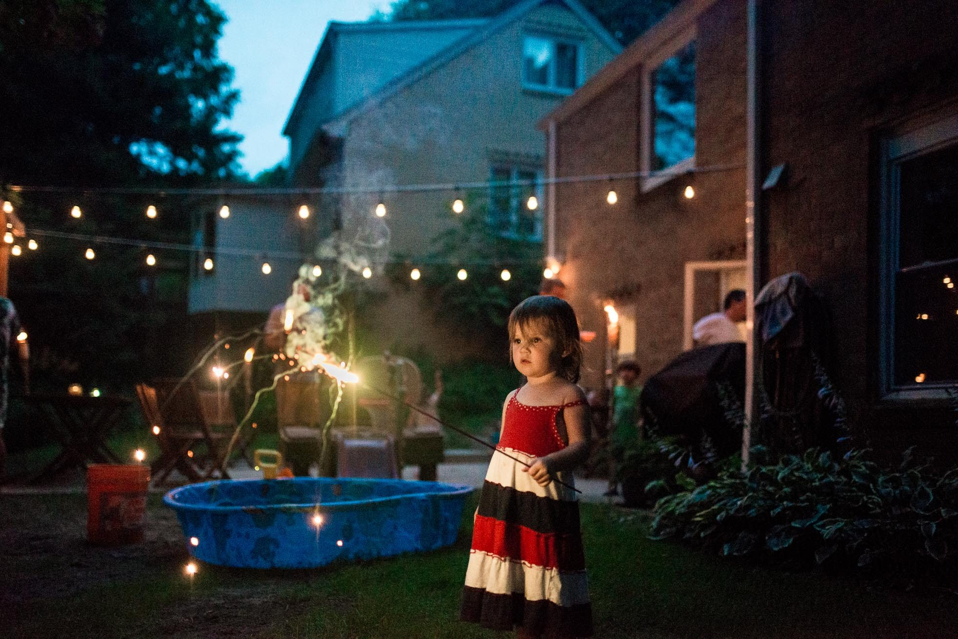 girl holding sparkler on fourth of july in the backyard
