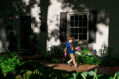 boy holding two purple squirt guns in front of house in dappled light