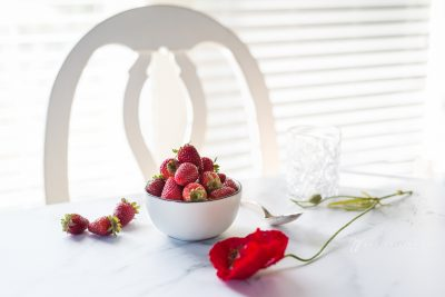a white bowl of strawberries and red poppy high key