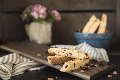 biscotti on a cutting board with linen and blue bowl