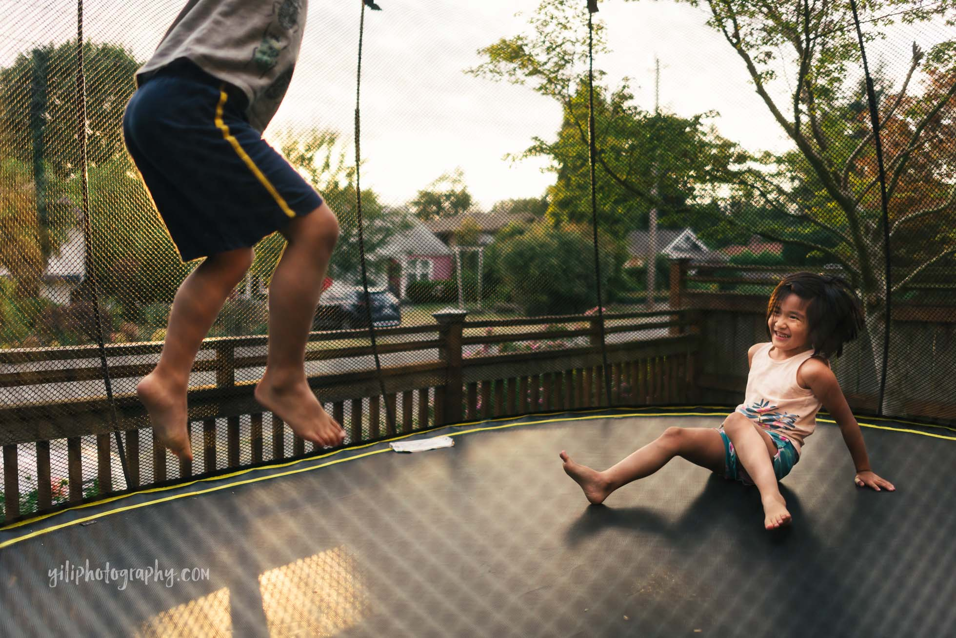 girl laughing on trampoline while her brother jumps next to her