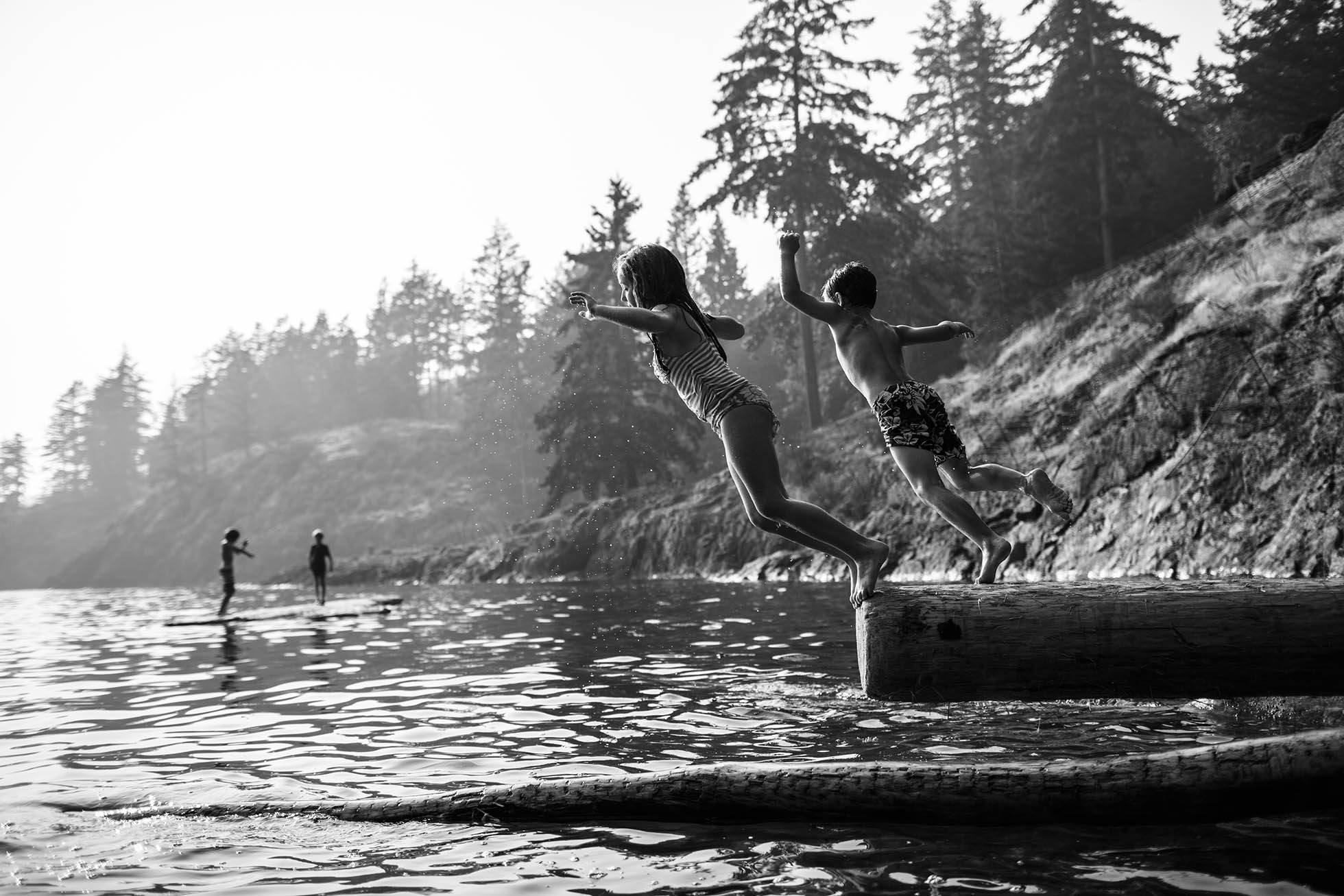 Siblings captured mid-jump while playing on the logs that washed up into an island cove British Columbia, Canada.