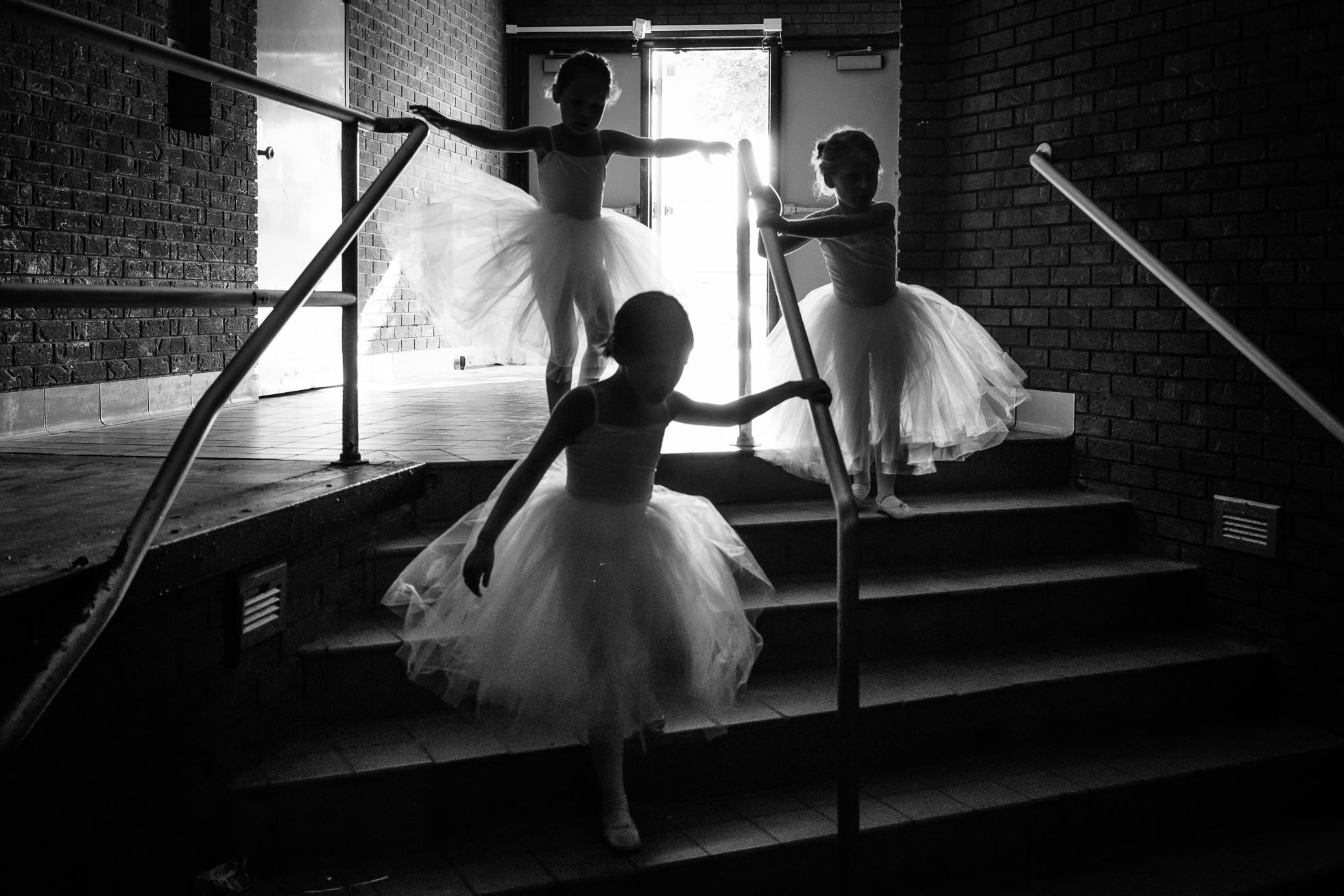three little ballerinas are at their ballet rehearsal captured in a real life photography style
