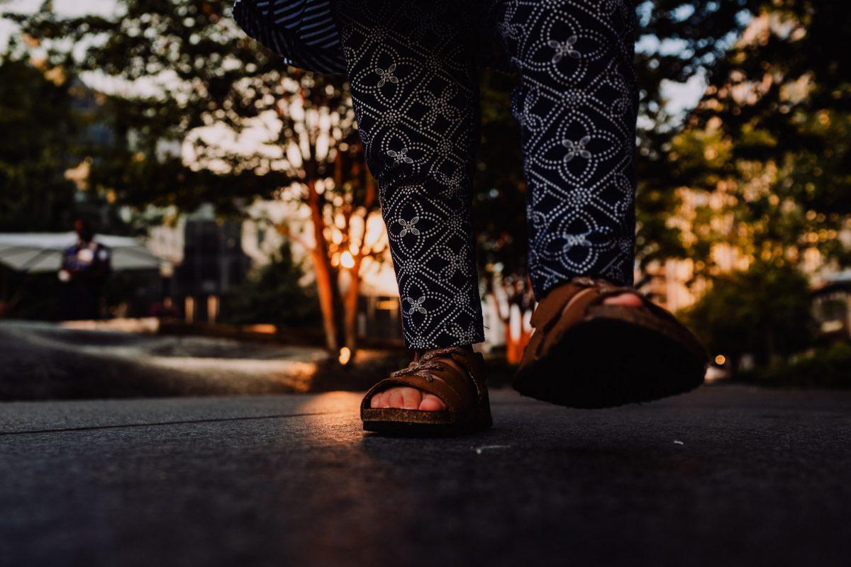 Golden hour documentary image of toddler walking feet.