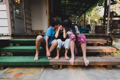 Three kids on steps kissing cheeks