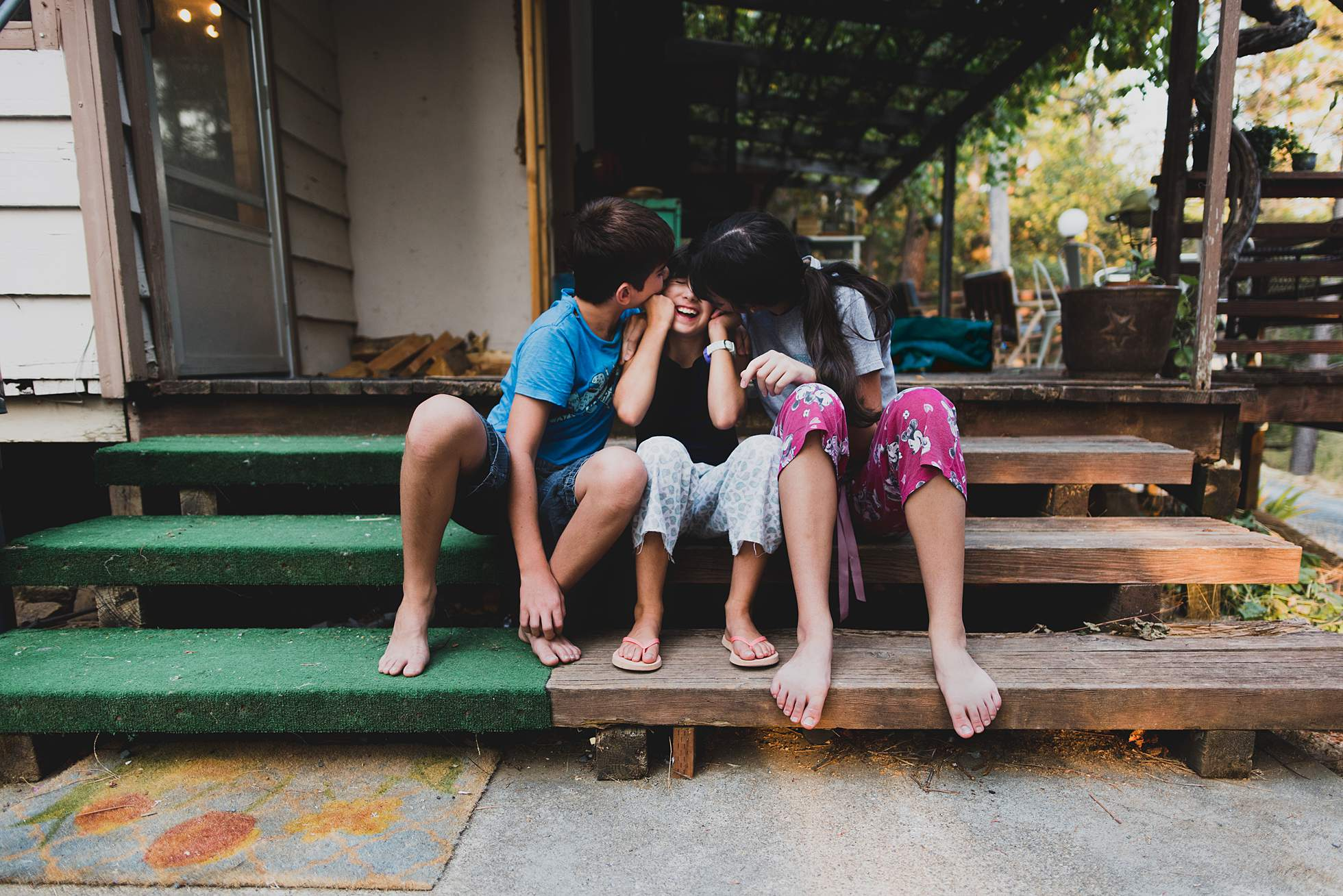 Three kids on steps kissing cheeks