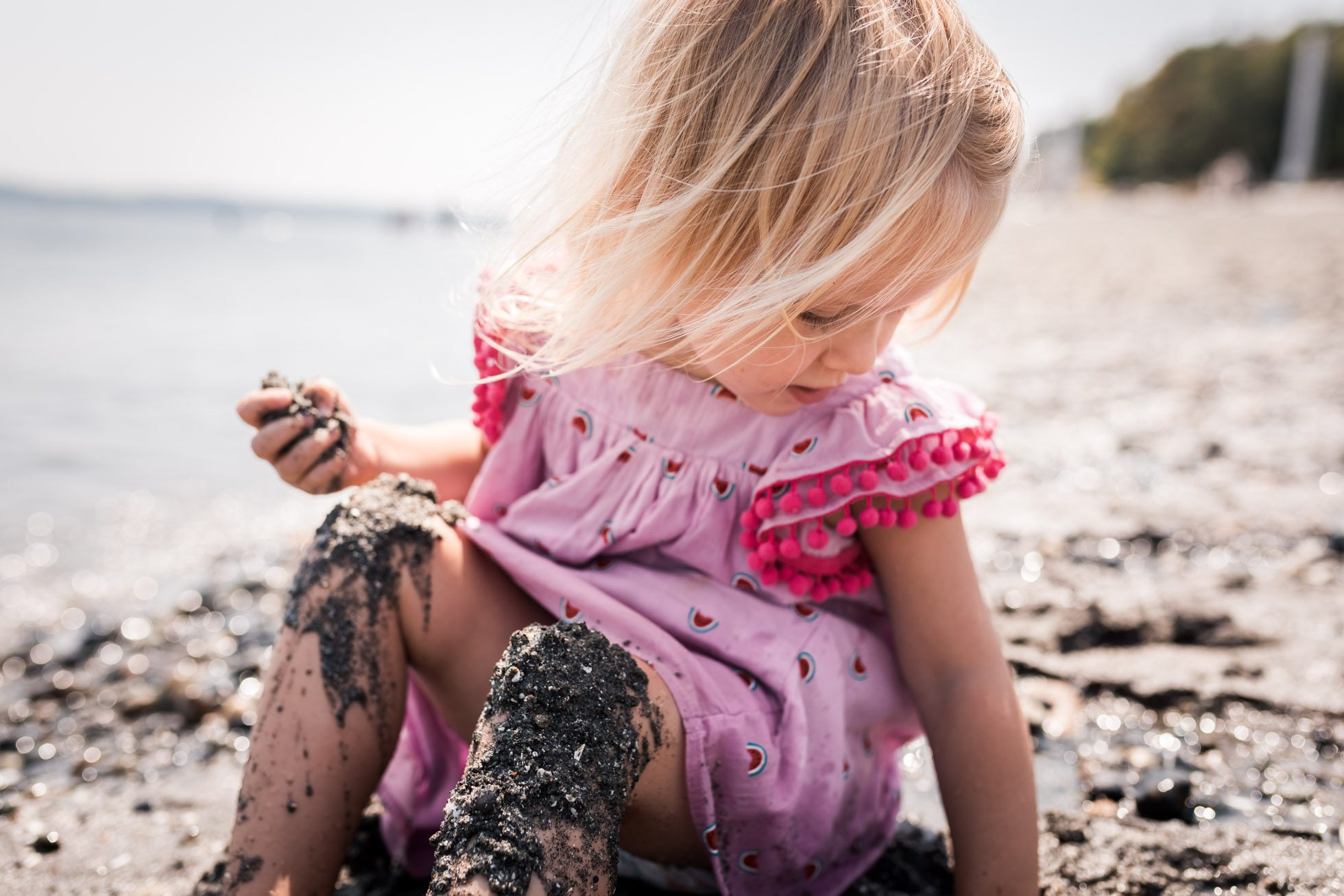 Little girl playing in sand on beach