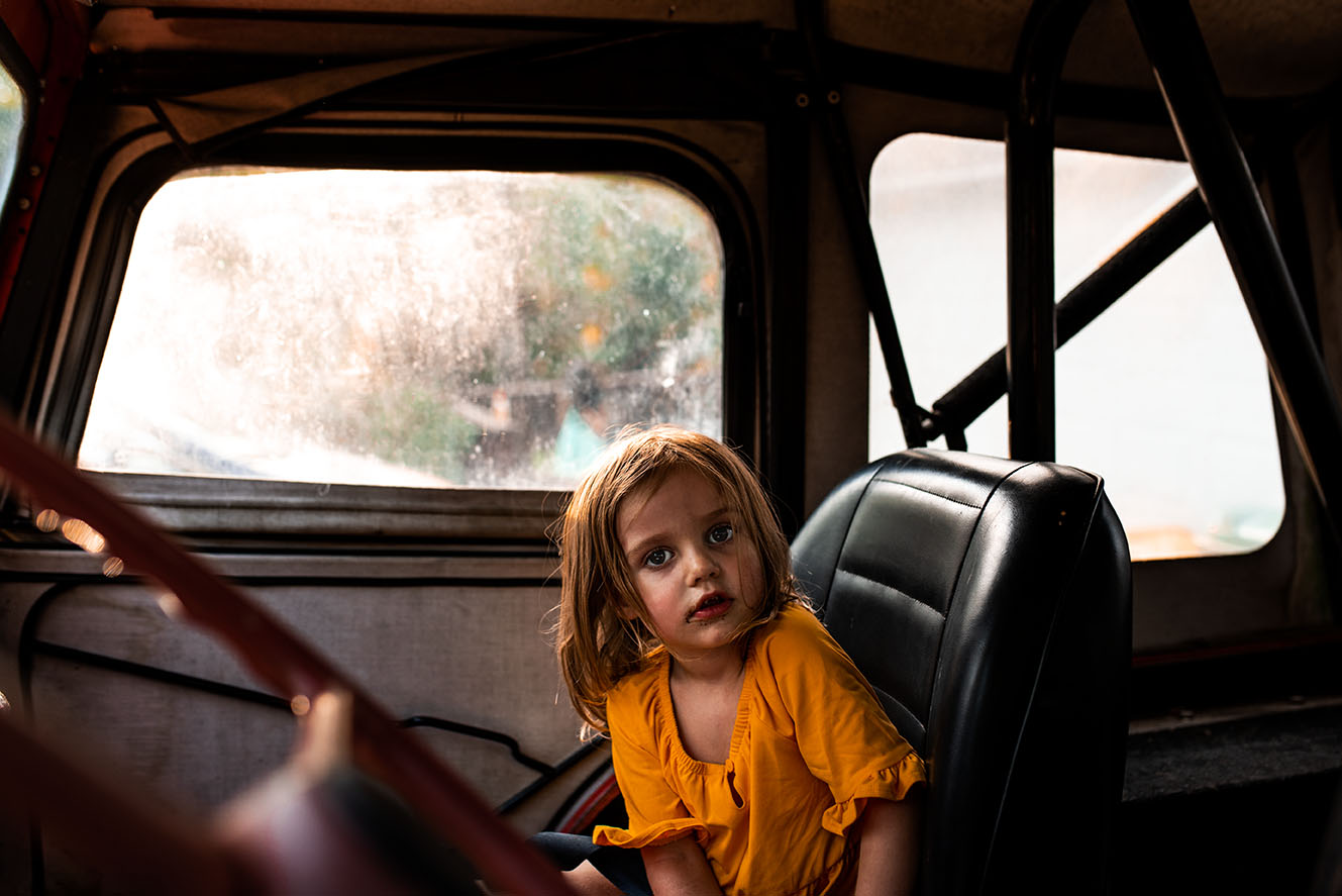 Documentary photograph of toddler in vintage jeep