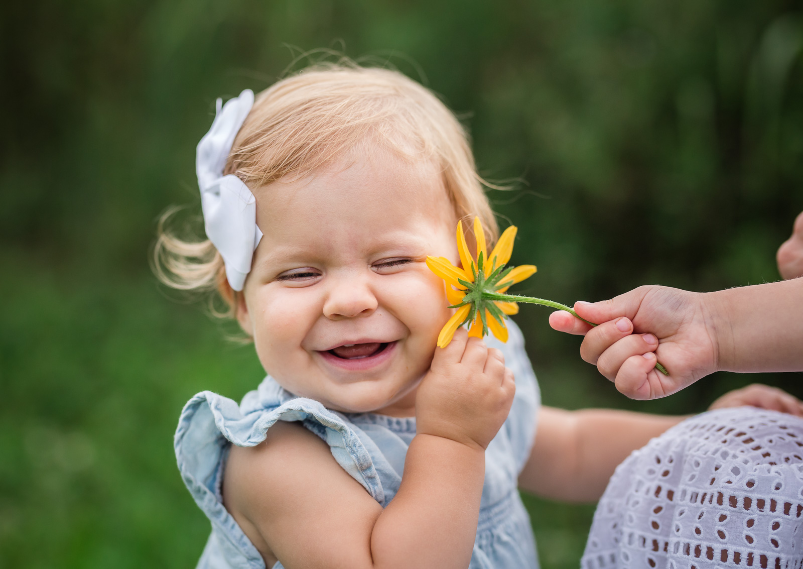 Big sister tickles little sister with flower