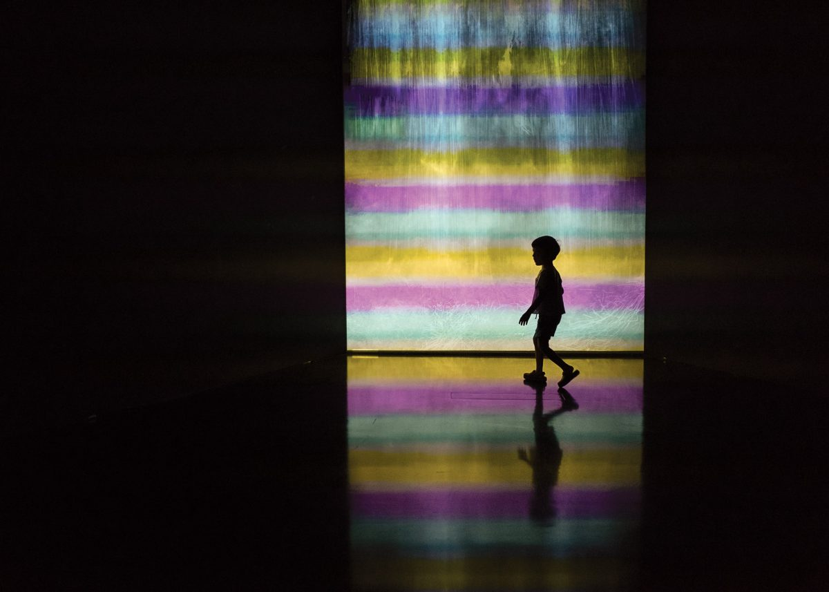 child walking against a rainbow wall in the museum