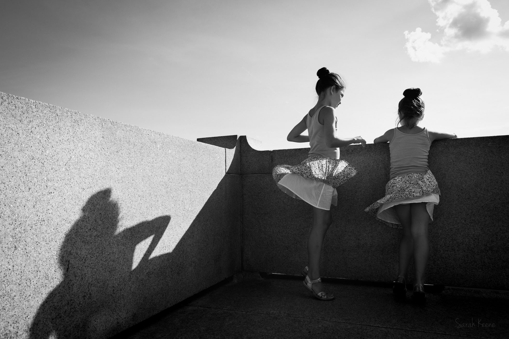 Windy-day-two-girls-skirts-fly-up-by-Sarah-Keene